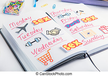 Close up Planning Organizer with colourful pictures of actions on the working place. Creative conceptual image of day planning in daily life. Selective focus.