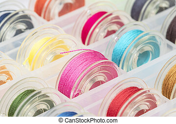 Close up plastic sewing machine bobbins with colourful thread in plastic box.