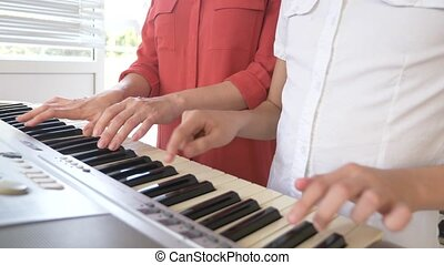 close-up. playing the piano in four hands. feminine and child's hands play together on a synthesizer. 4k, slow motion