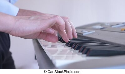 close-up. playing the piano in four hands. feminine and masculine hands play together on a synthesizer. 4k, slow motion