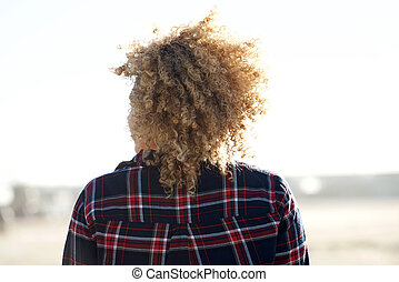 behind of african american woman with curly hair outdoors