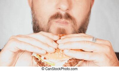 close up portrait man eats burger