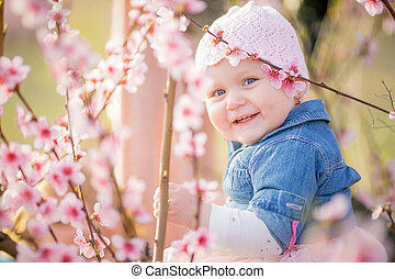Close-up portrait of a 1-2 year old girl outdoors in a garden with pink flowers in the trees