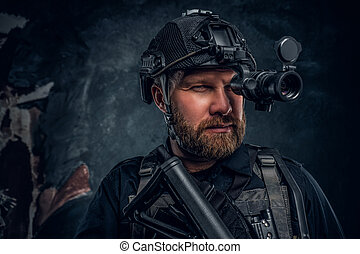 Close-up portrait of a bearded special forces soldier observes the surroundings in night vision goggles.