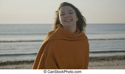 Close up portrait of a beautful young girl smiling on the beach while wind blows her hair