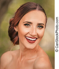 portrait of a beautiful bride on the background of spring foliage