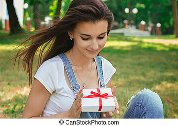 close-up portrait of a beautiful brunette with a gift in the hands