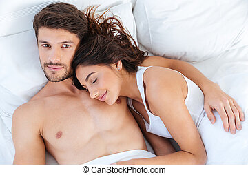 Close-up portrait of a beautiful couple lying in bed
