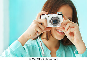 Close up portrait of a beautiful cute teen girl with digital photo camera
