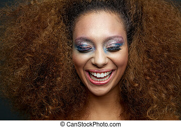Close up portrait of a beautiful female fashion model with colorful make up and curly hairstyle