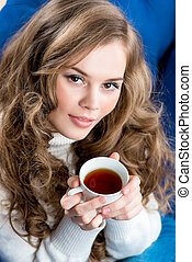 close-up portrait of a beautiful girl with a cup of tea on the couch