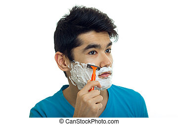 close-up portrait of a beautiful guy with foam on his face who shaves his beard