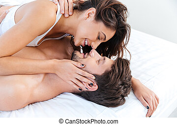Close-up portrait of a beautiful married couple on bed at...