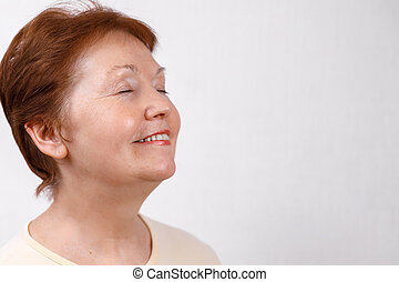 close-up portrait of a beautiful senior woman looking to the side on a white background in a light T-shirt. isolated