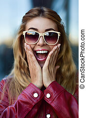 Close up portrait of a beautiful smiling girl in sunglasses with nice teeth having fun at street.