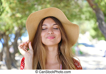 Close up portrait of a beautiful smiling girl with closed eyes wearing a hat enjoying peace outdoor