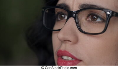 Close-up portrait of a beautiful woman in glasses who utters words.