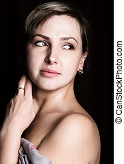 close-up portrait of a beautiful woman with bare shoulders on a dark background