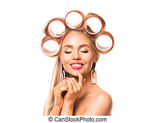 Close up portrait of a beautiful woman with hair rollers on white background.