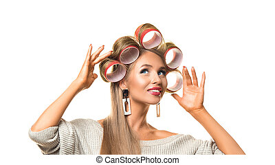 Close up portrait of a beautiful woman witn a hair curlers on white background.