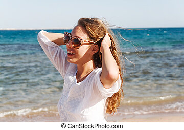 close-up portrait of a beautiful young brunette girl with long hair on a background of blue sea with waves and sky with clouds on a sunny day, lifestyle, posing and smiling, wind