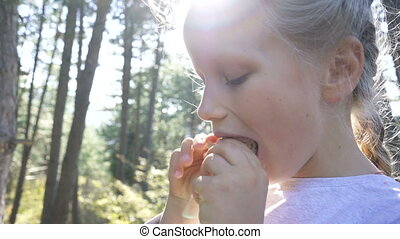 Close up portrait of a beautiful young girl enjoying and eating a fresh sandwich during a summer holiday.