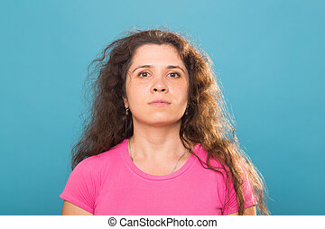 Close up portrait of a beautiful young woman with curly hair on blue background