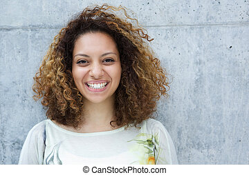 Close up portrait of a beautiful young woman with curly hair smiling outdoors