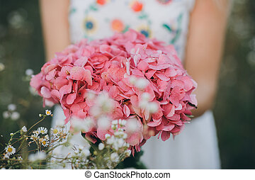 Close up portrait of a beauty blonde girl with long hair, holds a bouquet of pink flowers