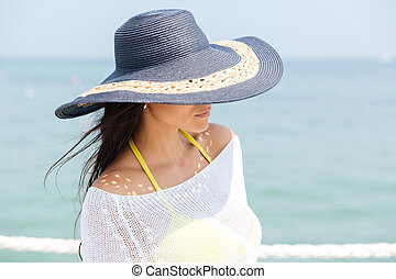 Close-up portrait of a brunette girl in hat outdoors