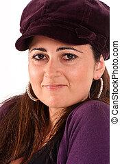 Close-up portrait of a brunette wearing a cap