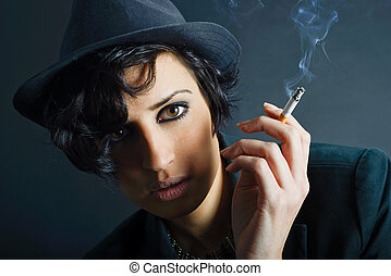 Close-up portrait of a brunette woman smoking a cigarette on black background wearing a hat