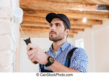 Close-up portrait of a builder worker painting wall indoors...