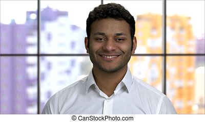 Close up portrait of a cheerful hindu man smiling with teeth. Wearing white formal shirt. Window background.