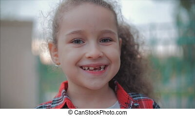 Close-up portrait of a cute happy Caucasian little girl making a surprised face and then smiling looking at the camera enjoying a warm summer day at sunset.