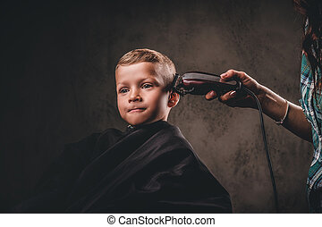 Close-up portrait of a cute preschooler boy getting haircut on the dark background.