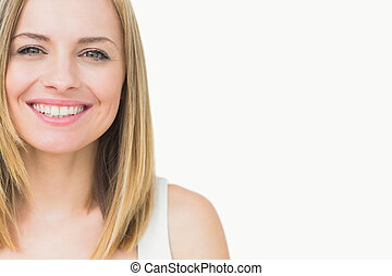 Close-up portrait of a cute young woman smiling over white ...