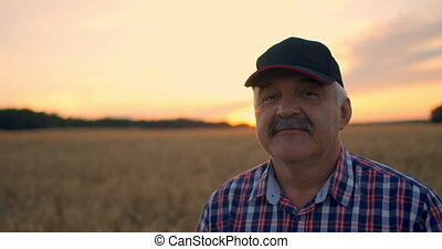 Close-up portrait of a farmer in a cap at sunset looking directly into the camera