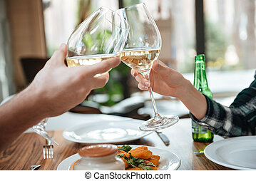 Close up portrait of a female and male hands toasting with...