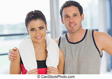 Close-up portrait of a fit couple in exercise room -...