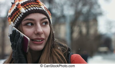 Close-up portrait of a funny girl talking on her mobile...