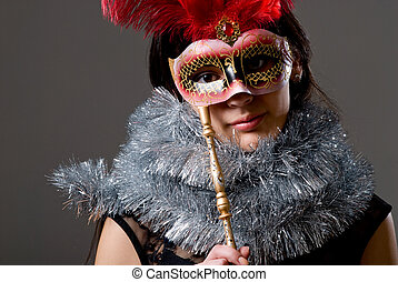 Close-up portrait of a girl in a mask with red feathers and tinsel. On a gray background