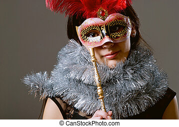 Close-up portrait of a girl in a mask with red feathers and tinsel.