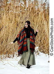 Close-up portrait of a girl in winter among cane.