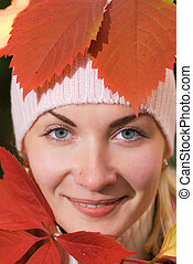 Close-up portrait of a girl with autumn leaves