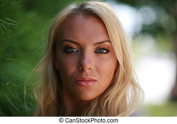 Close-up portrait of a gorgeous blond woman outdoors. Shallow DOF.