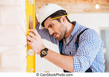 Close-up portrait of a handsome pensive builder holding level