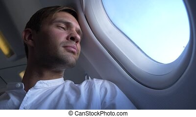 close-up. portrait of a handsome young man who looks at the airplane window during the flight.