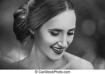 portrait of a happy bride on the background of spring foliage