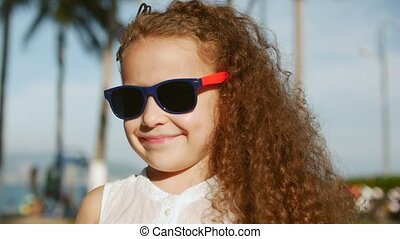 Close-up portrait of a happy cute little girl child with curly hair and red sunglasses looking into the camera
